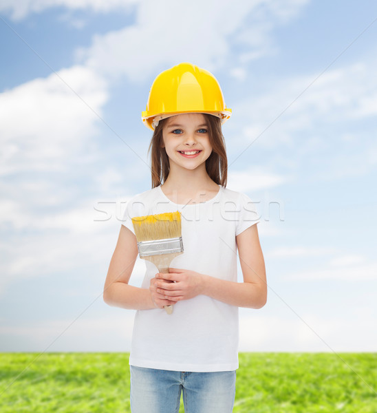 smiling little girl in helmet with paint brush Stock photo © dolgachov