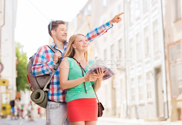 smiling couple with city guide and backpack Stock photo © dolgachov