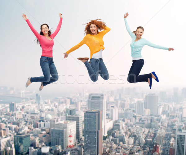 group of smiling women jumping in air Stock photo © dolgachov