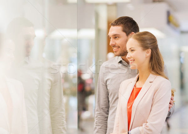 happy couple looking to shop window in mall Stock photo © dolgachov