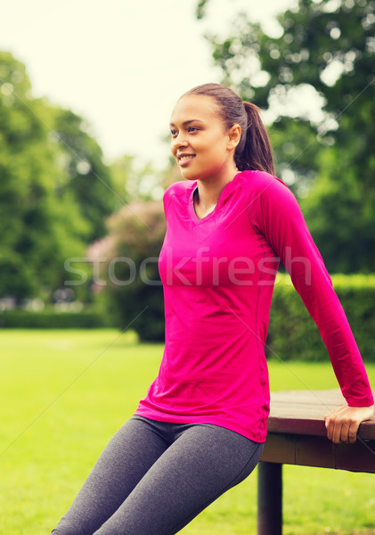 smiling woman doing push-ups on bench outdoors Stock photo © dolgachov