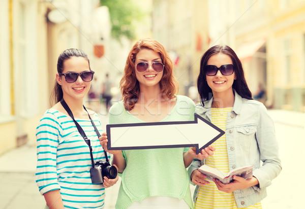 smiling teenage girls with white arrow outdoors Stock photo © dolgachov