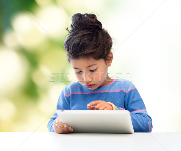 little girl with tablet pc over green background Stock photo © dolgachov