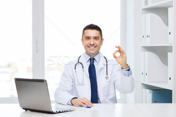 smiling doctor with laptop showing ok in office Stock photo © dolgachov