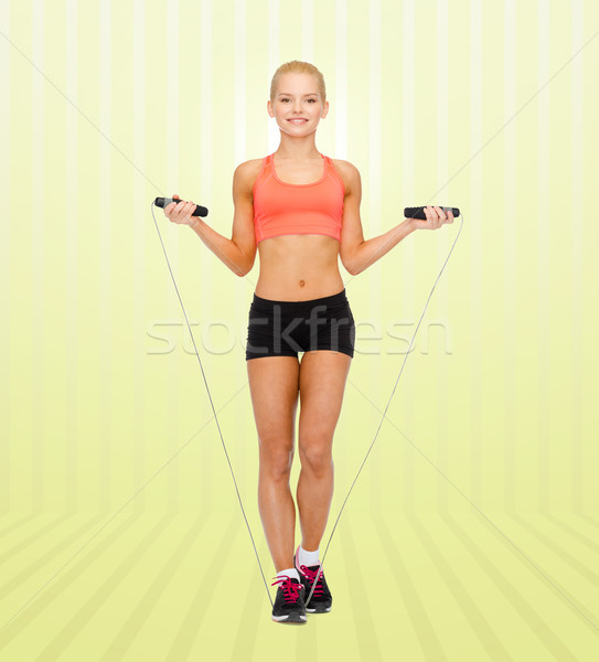 smiling sporty woman jumping with skipping rope Stock photo © dolgachov