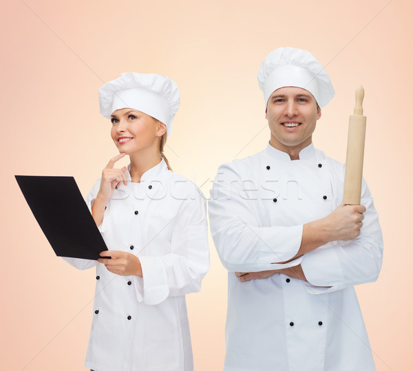 happy chefs or cooks couple holding rolling pin Stock photo © dolgachov