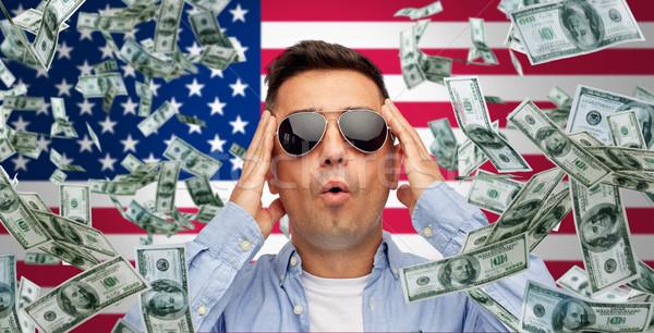 surprised man under money rain over american flag Stock photo © dolgachov