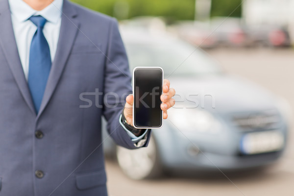 Stock photo: close up of business man with smartphone and car