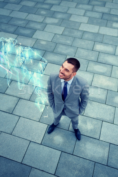 Empresário mapa do mundo holograma ao ar livre negócio desenvolvimento Foto stock © dolgachov