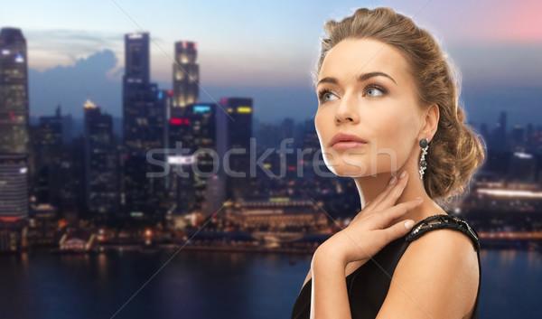 beautiful woman wearing earrings over evening city Stock photo © dolgachov