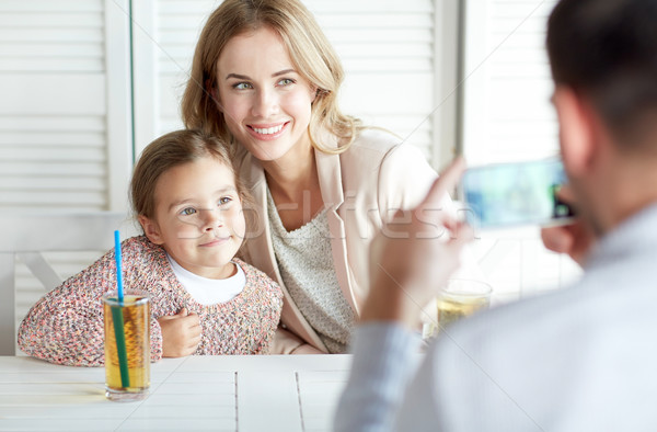 happy family picturing by smartphone at restaurant Stock photo © dolgachov