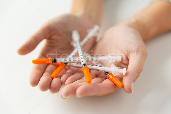close up of woman hands holding insulin syringes Stock photo © dolgachov
