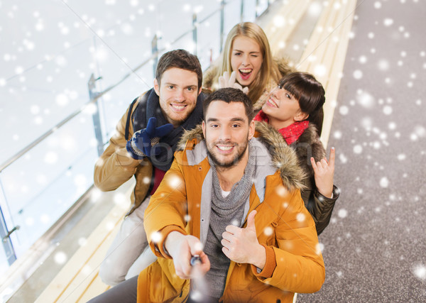 Stock photo: happy friends taking selfie on skating rink