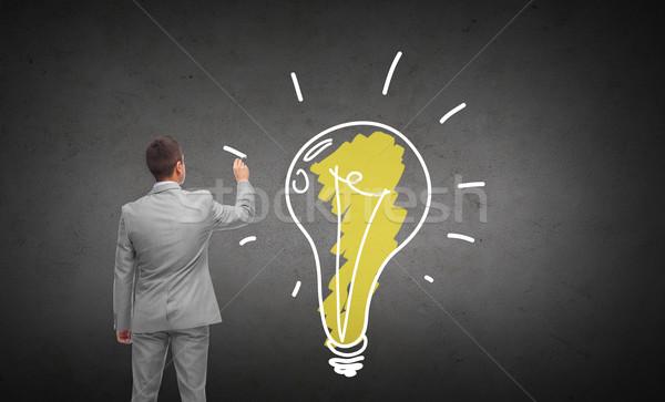 businessman drawing lighting bulb from back Stock photo © dolgachov