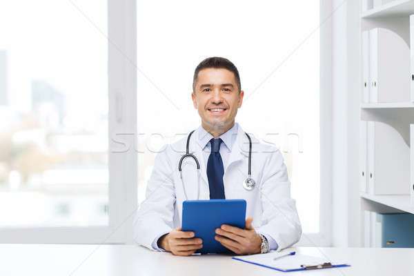 smiling male doctor in white coat with tablet pc Stock photo © dolgachov