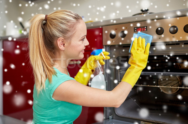 happy woman cleaning cooker at home kitchen Stock photo © dolgachov