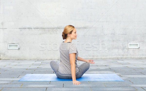 woman making yoga in twist pose on mat outdoors Stock photo © dolgachov