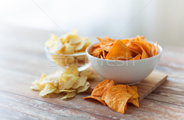 Stock photo: close up of potato crisps and nachos in glass bowl