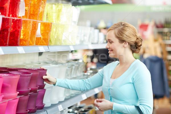 happy woman choosing flower pot in store Stock photo © dolgachov