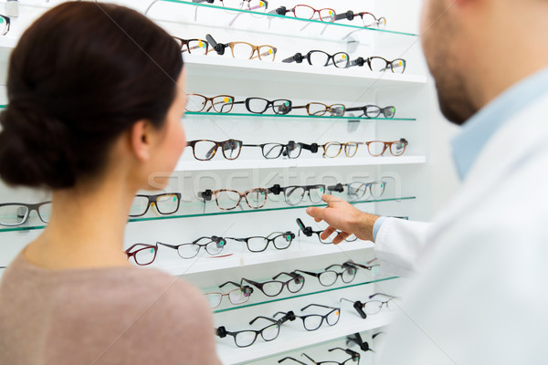 optician showing glasses to woman at optics store Stock photo © dolgachov