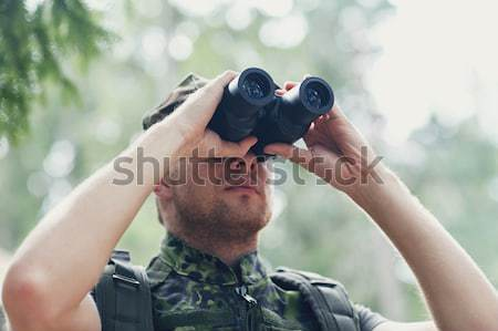 soldier or hunter shooting with gun in forest Stock photo © dolgachov
