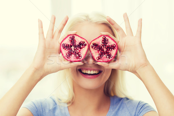 happy woman covering eyes with pomegranate Stock photo © dolgachov