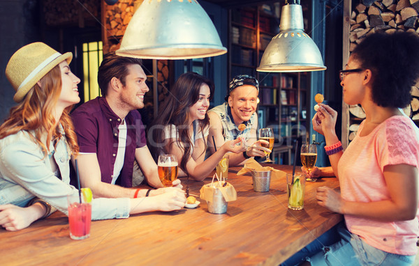 happy friends with drinks talking at bar or pub Stock photo © dolgachov