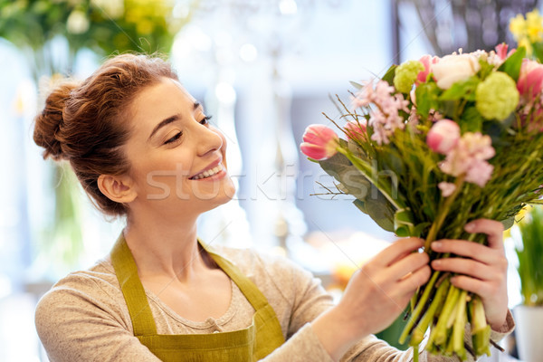 smiling florist woman making bunch at flower shop Stock photo © dolgachov