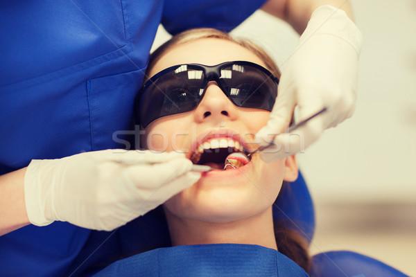 female dentist checking patient girl teeth Stock photo © dolgachov