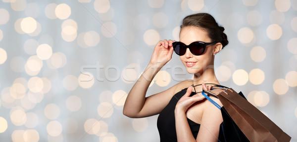 Stock fotó: Boldog · nő · fekete · napszemüveg · bevásárlótáskák · vásár