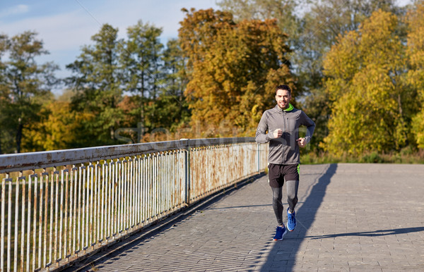 happy young man running over city bridge Stock photo © dolgachov