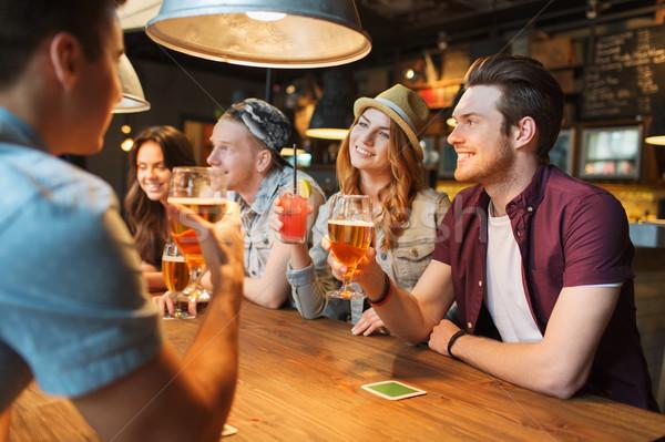 happy friends with drinks talking at bar or pub Stock photo © dolgachov