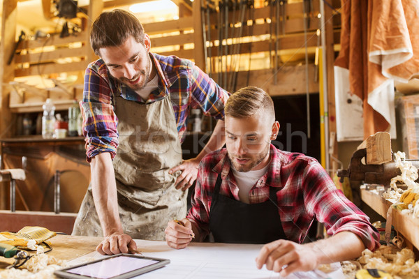 Stock photo: workmen with tablet pc and blueprint at workshop