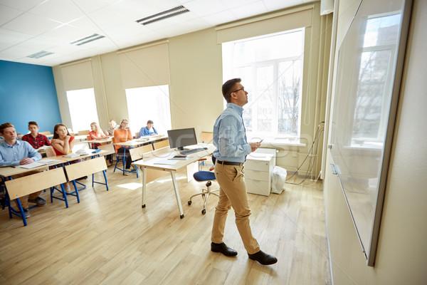 students and teacher writing on school white board Stock photo © dolgachov