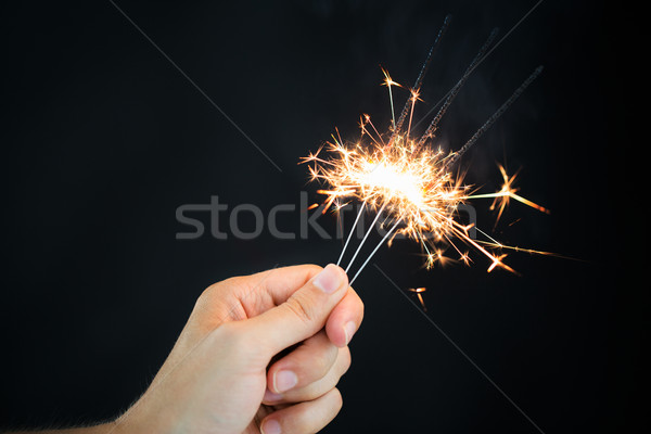 hand holding sparklers over black background Stock photo © dolgachov