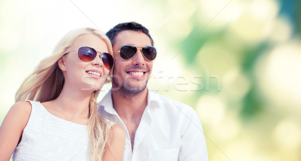 happy couple in shades over green background Stock photo © dolgachov
