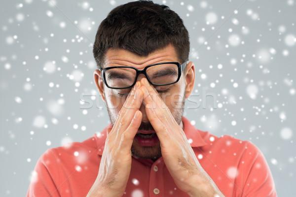 tired man with eyeglasses touching his nose bridge Stock photo © dolgachov