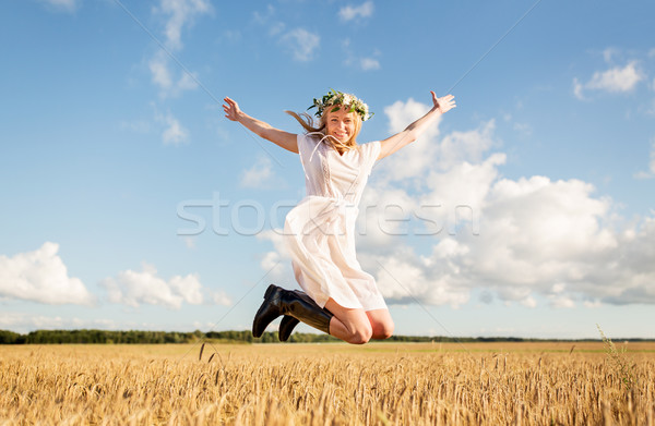 happy woman in wreath jumping on cereal field Stock photo © dolgachov