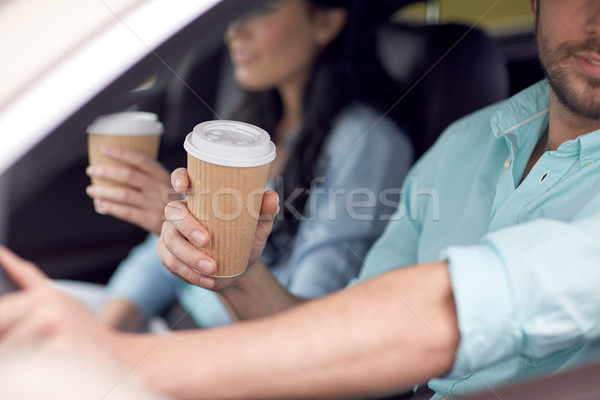 close up of couple driving in car with coffee cups Stock photo © dolgachov