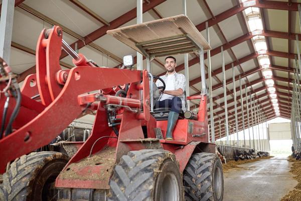 man or farmer driving tractor at farm Stock photo © dolgachov