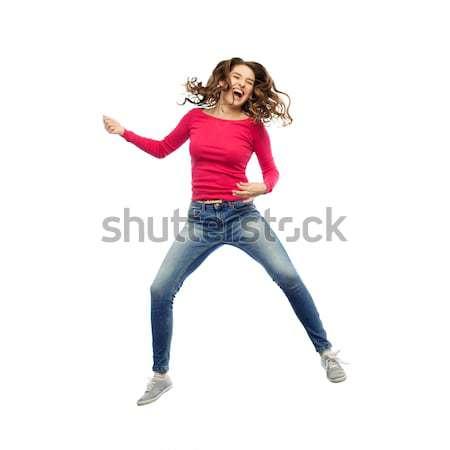 happy woman jumping and pretending guitar playing Stock photo © dolgachov