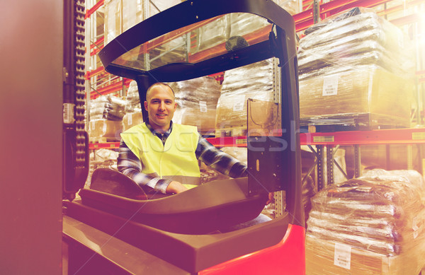 smiling man operating forklift loader at warehouse Stock photo © dolgachov
