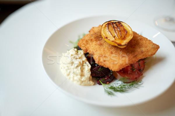 close up of fish salad with roasted lemon on plate Stock photo © dolgachov
