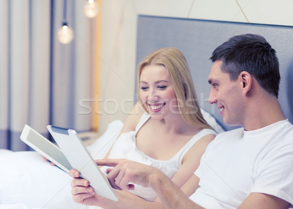 smiling couple in bed with tablet pc computers Stock photo © dolgachov