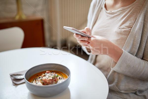 женщину смартфон тыква суп кафе продовольствие Сток-фото © dolgachov