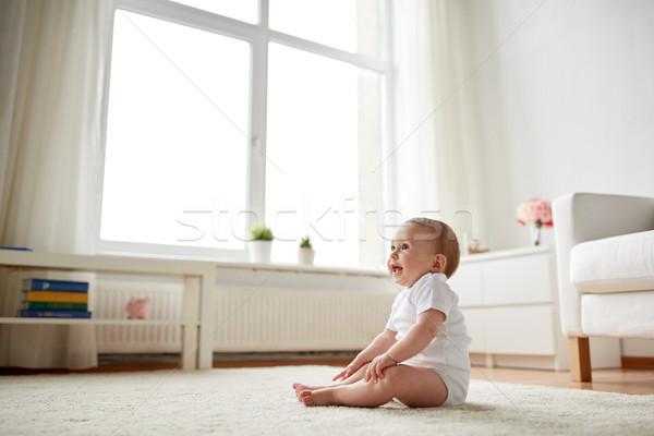 happy baby boy or girl sitting on floor at home Stock photo © dolgachov