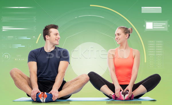 happy sportive man and woman sitting on mats Stock photo © dolgachov