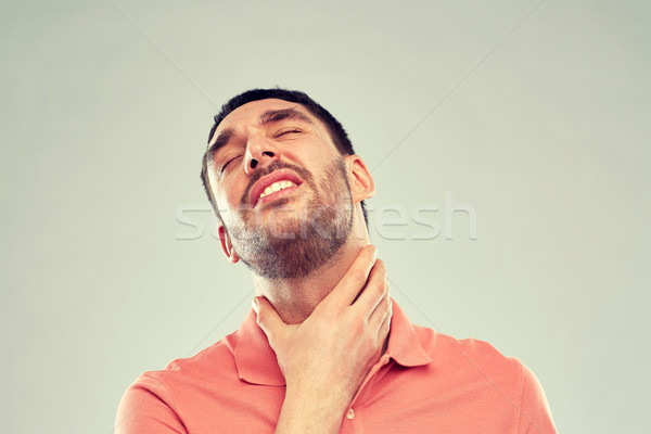 man touching neck and suffering from throat pain Stock photo © dolgachov