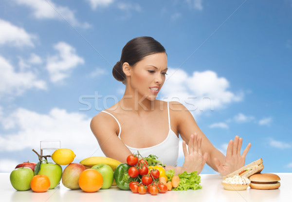 woman with fruits rejecting fast food Stock photo © dolgachov
