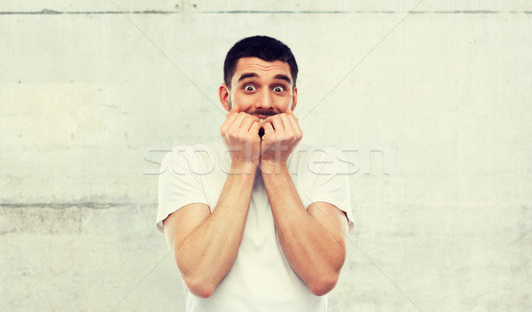 scared man in white t-shirt over gray wall Stock photo © dolgachov
